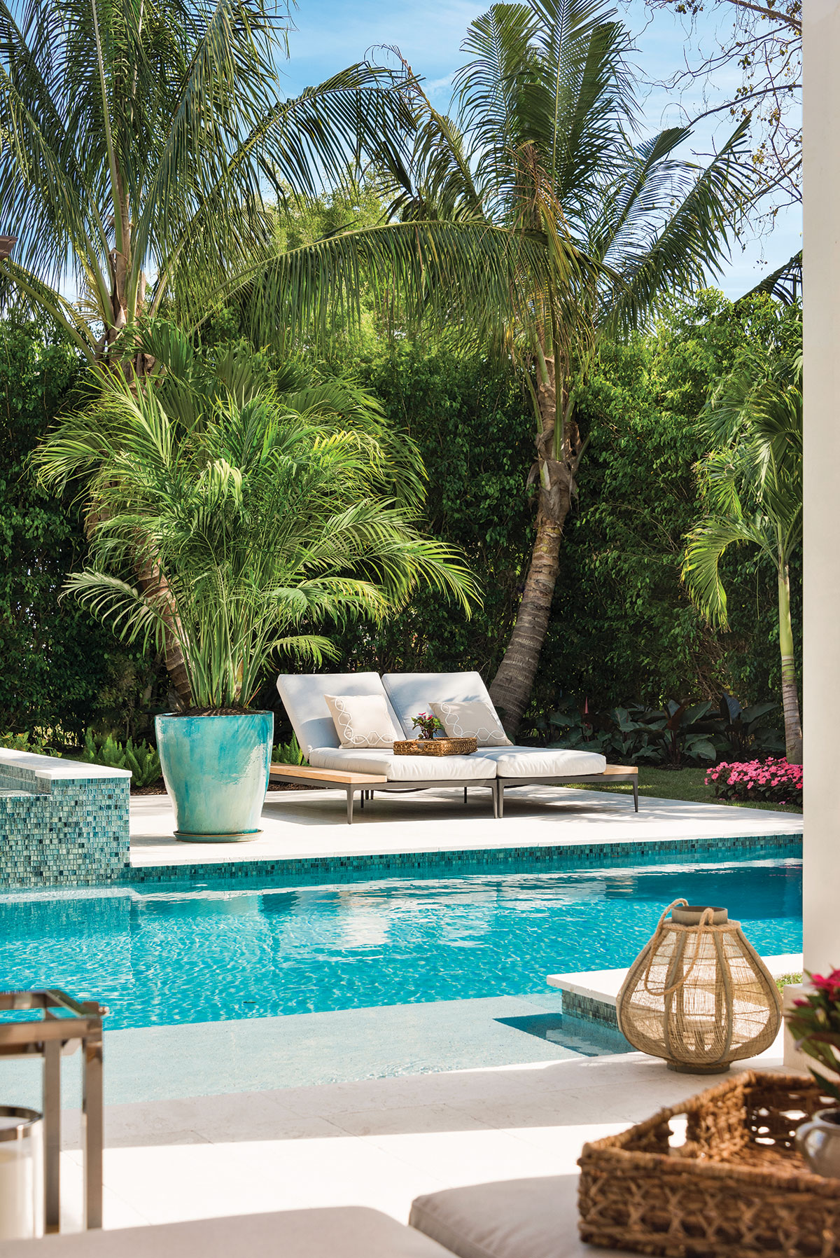Lounge chairs from Gloster Furniture adorned with accent pillows from Calusa Bay Design surround a sparkling pool lined with mosaic tiles from Ceramic Matrix.