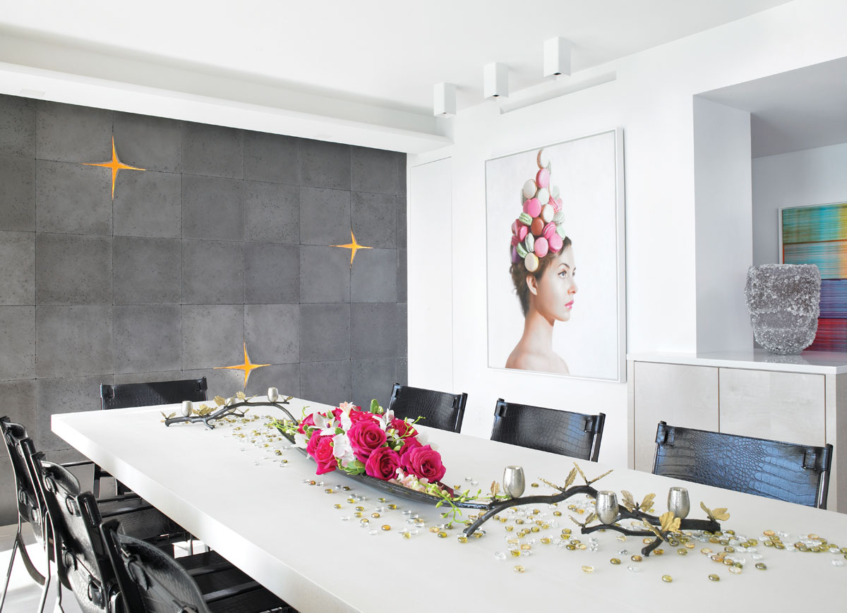 "In the dining area, an intriguing glass centerpiece branches out across a Christian Liaigre dining table, where Fendi Casa's ""Blixen"" dining chairs with hide belts and gunmetal gray buckles pull up to join the party. A dynamic composition of three-dimensional Kwa concrete tiles by Itai Bar-On from Ann Sacks covers a focal wall, while a whimsical painting, The Macaron Hat by artist Will Cotton, adds the perfect touch of flavor."