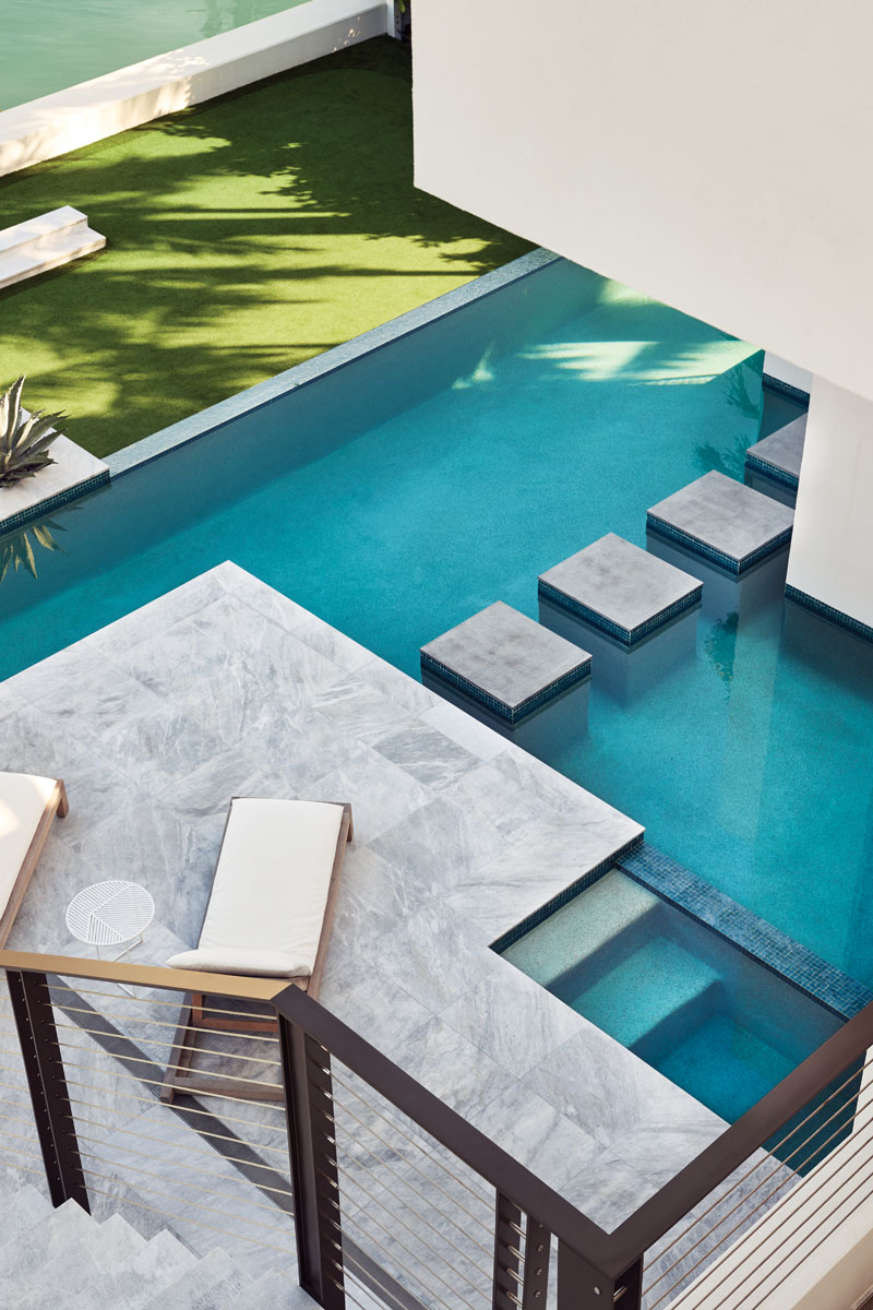 Columns inset into the custom swimming pool lead the way to the outdoor deck of the master suite.