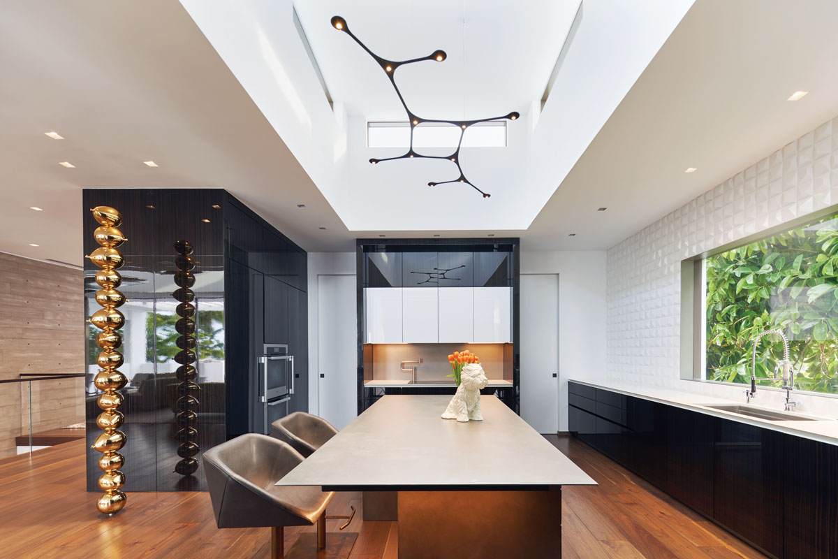 """Eggersmann USA cabinetry lines the kitchen. The center island is fabricated with cold rolled steel, while Caesarstone tops the base cabinets. Playing with light and shadow, Wow's 3D tile from Hastings frames the picture window. The modular """"Carbon"""" pendant light from Tokio allows optimum illumination above a porcelain Puppy Edition 1 vase by artist Jeff Koons."""