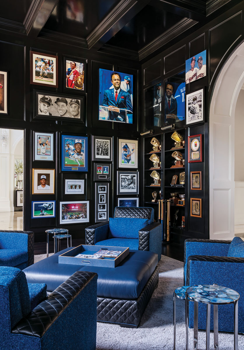 "In Roberto's study, memorabilia and awards gleaned during his 16-year baseball career pop from the black lacquered surfaces. ""The walls create a dramatic and masculine backdrop,"" interior designer Jennifer Marksberry says. ""The touches of blue honor Robbie's career with the Toronto Blue Jays."""