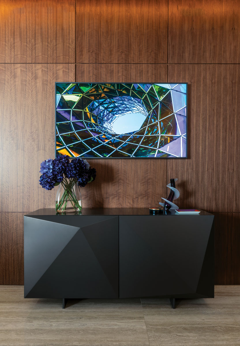 "Cattalan Italia's matte graphite cabinetry from Addison House styles the foyer in sleek, angular form. The ""Heechee Vase,"" a blown glass vessel by Thomas Kelly, blends with the colors of the photo art above."