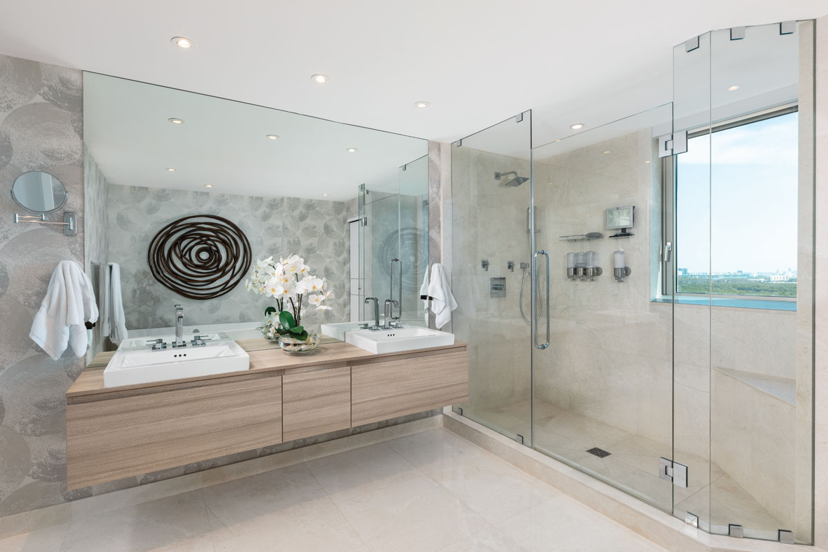 Circular art from Horshow adds visual interest in the master bath, where Orlean's wall covering swirls the private space in perfect complement. The glass-enclosed shower offers spa-like relaxation after a busy day.