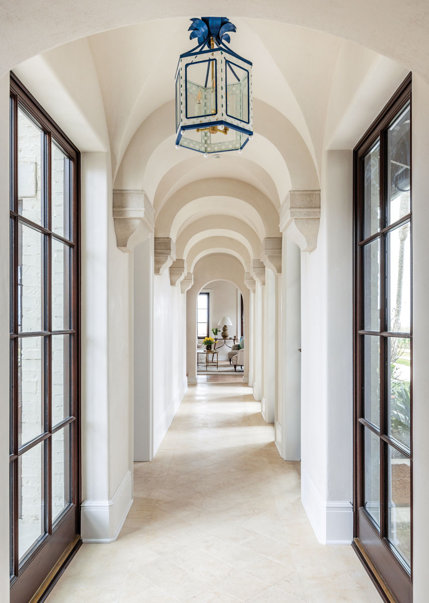 A dramatic hallway unites the newly remodeled entrance to the original home and features an entire wall of mahogany framed floor-to-ceiling windows that open onto the pool. The whimsical tole lantern overhead creates clever contrast to the grand architectural design.