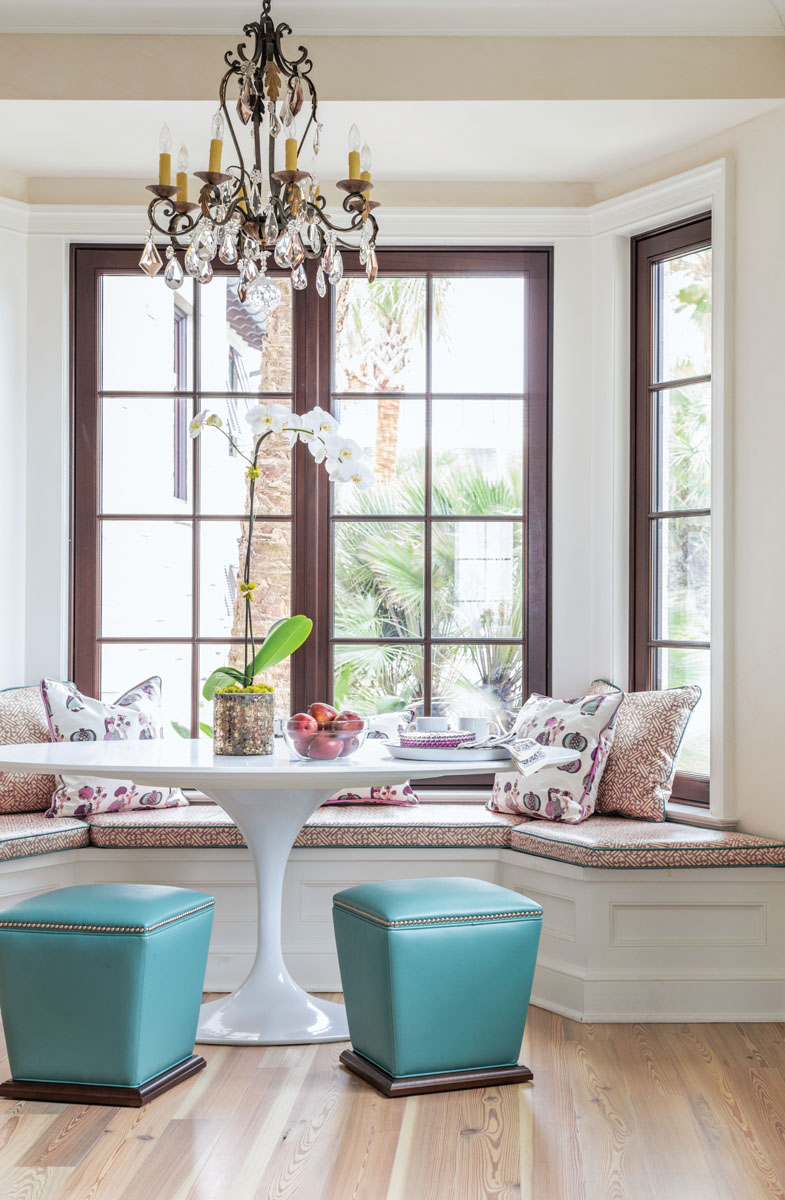 Nestled into a bay window just off the kitchen, a breakfast nook offers splendid views. A white tulip table from Rove Concepts is flanked with a pair of turquoise faux-leather ottomans from Lee Industries. An antique chandelier from Whitehall Antiques sparkles overhead.