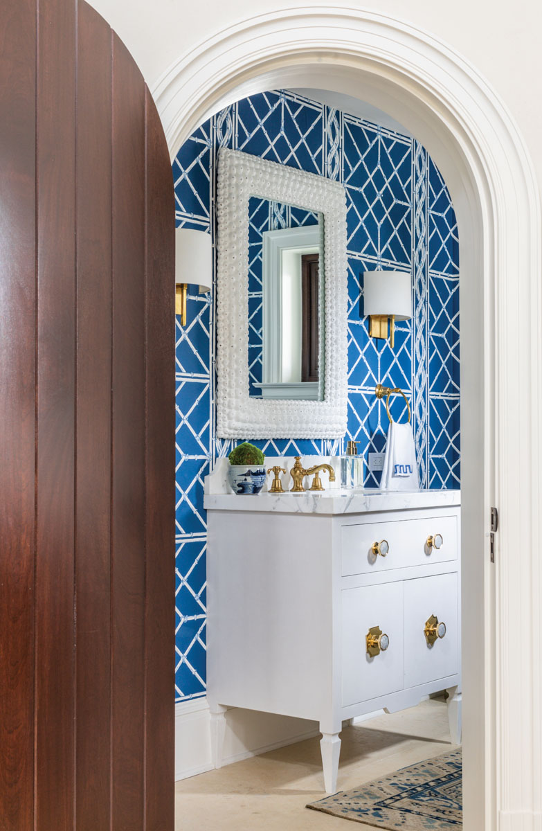 The powder room gets an intense dose of deep blue via a charming Chinese fretwork — patterned wall covering from the Palm Beach fabric firm of Bob Collins & Sons. A contemporary vanity from J. Tribble features large-scale brass and moonstone hardware by Addison Weeks.