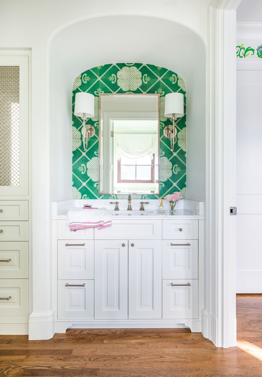 In the guest bath, painted wood tiles in vibrant shades of green accentuate an arched niche that houses a custom Beaches Woodcrafts vanity lighted with Hudson Valley wall lamps.