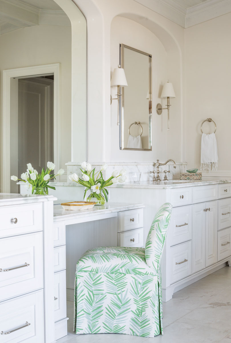 Inspired by a stunning marble that features a subtle green veining, the master bath follows suit with the upstairs color scheme. A linen fern-print from Duralee in a fresh green hue dresses the elegant vanity chair from Ballard Designs.