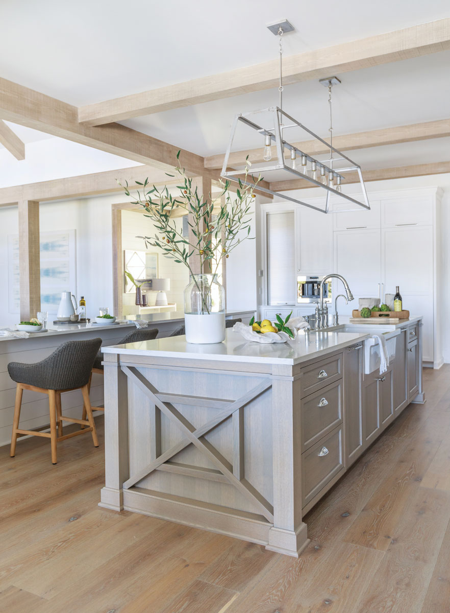 Two islands define the clean and simple kitchen — one amply suited for food prep; the other a streamlined breakfast bar lined with Palecek's woven counter stools.