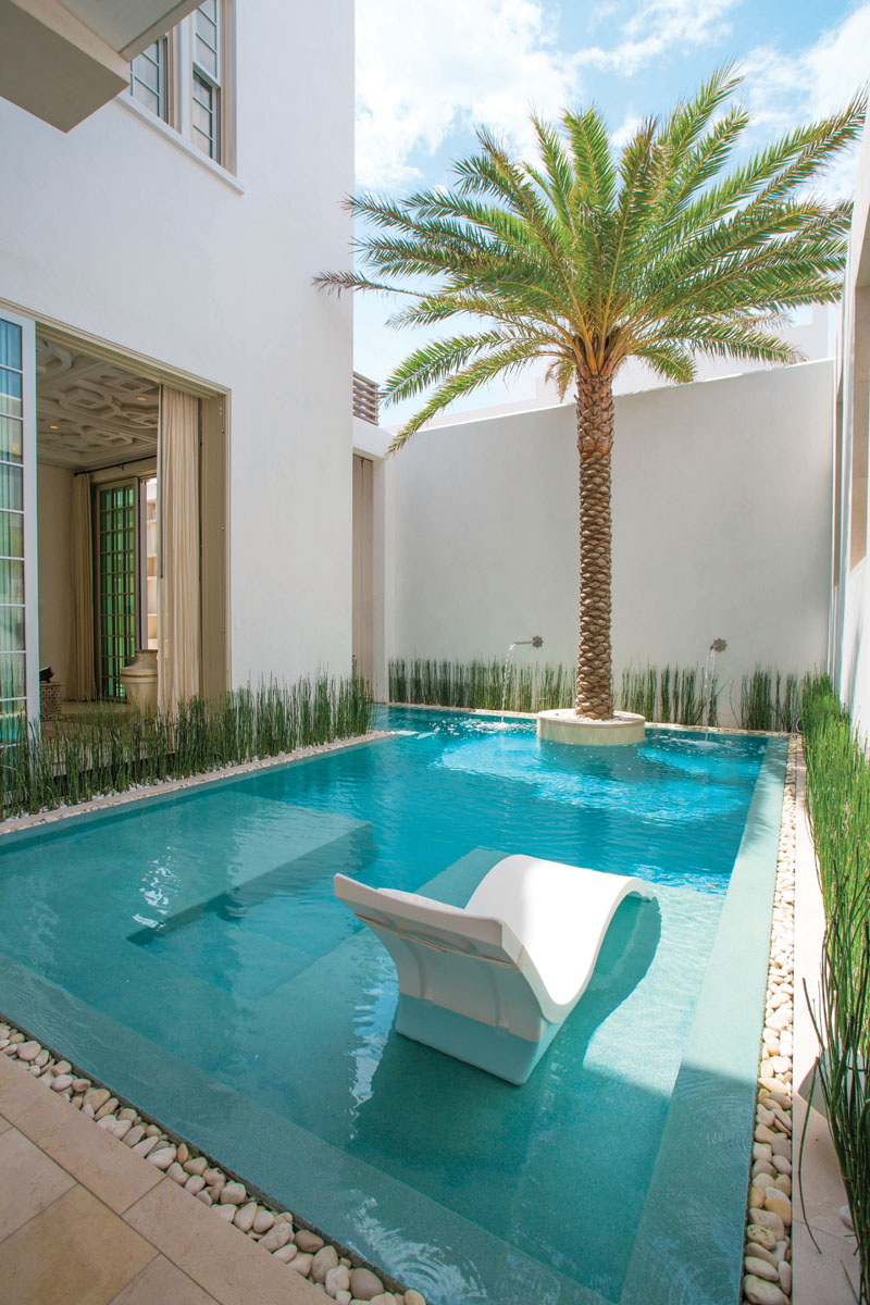 A rimless pool beckons as it steps down and wraps around an island palm on its way to the courtyard's floating pavilion.