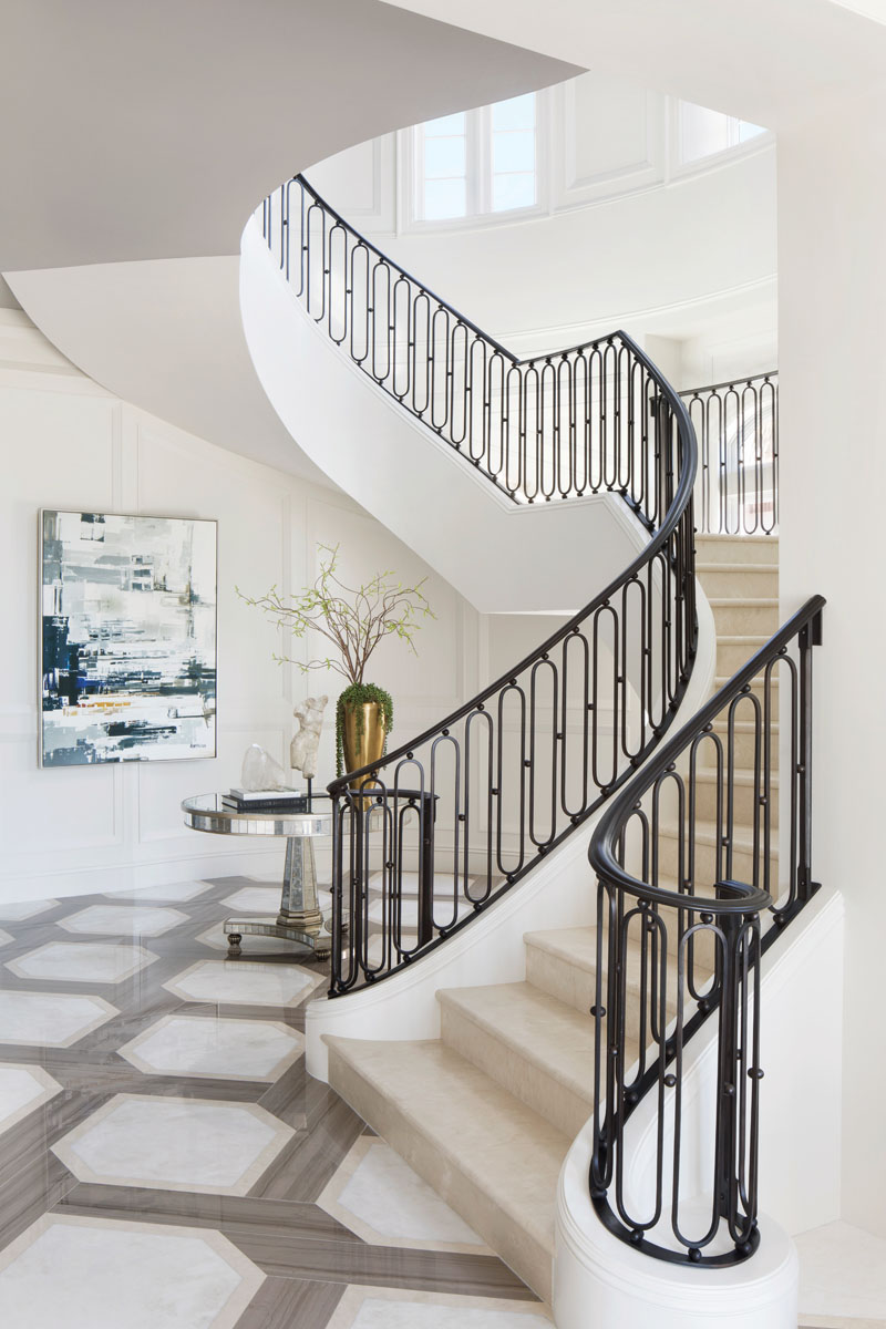The traditional grandeur of the stairway announces entry to the home, while an abstract, Let It All Fall Off, adds a touch of modern. Century Furniture's antiqued mirror and gold leaf receiving table center the foyer.