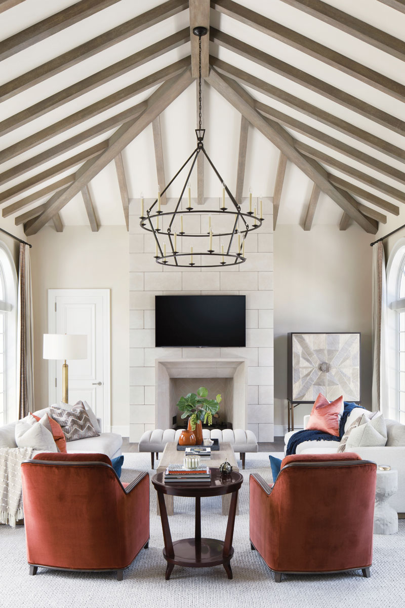 With significant scale, a two-tiered, ring chandelier in aged iron holds its own in the family room. Here, Rowe's sofas; lounge chairs from Palecek; bench from Arteriors.