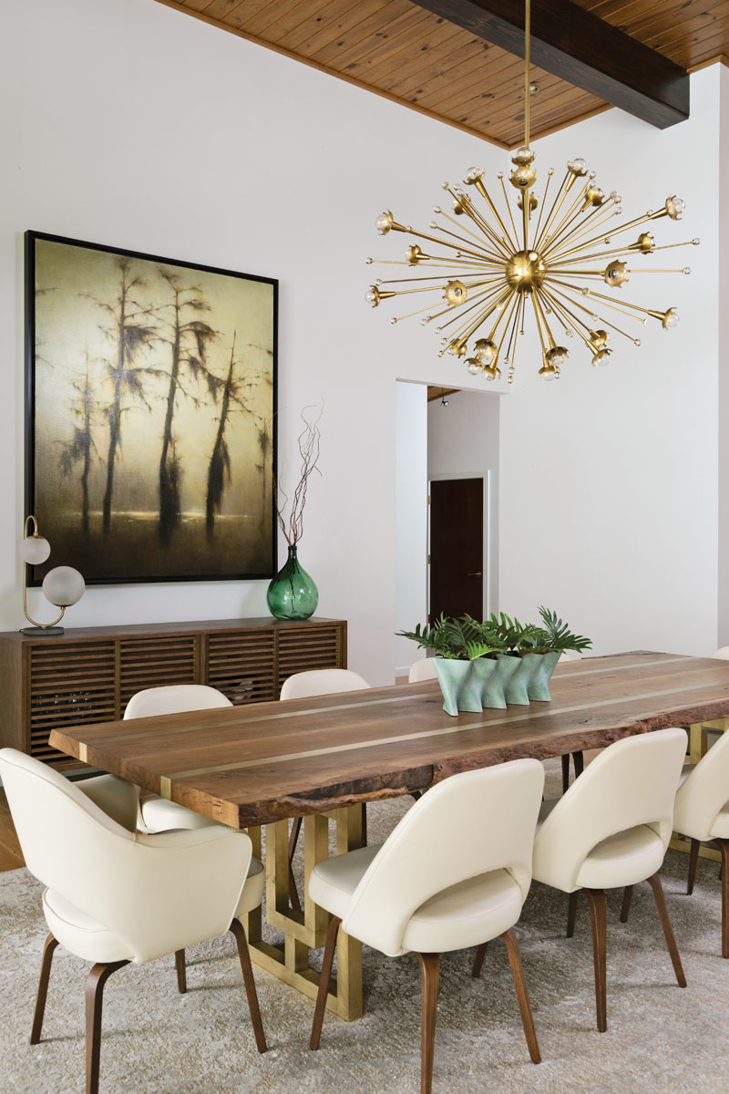 "Jonathan Adler's ""Sputnik"" chandelier sparkles above Eero Saarinen chairs from DWR. Designed by the homeowners' son, Johnny Laderer, the table is handcrafted by BUILT from a live oak tree that had to be removed from the property."