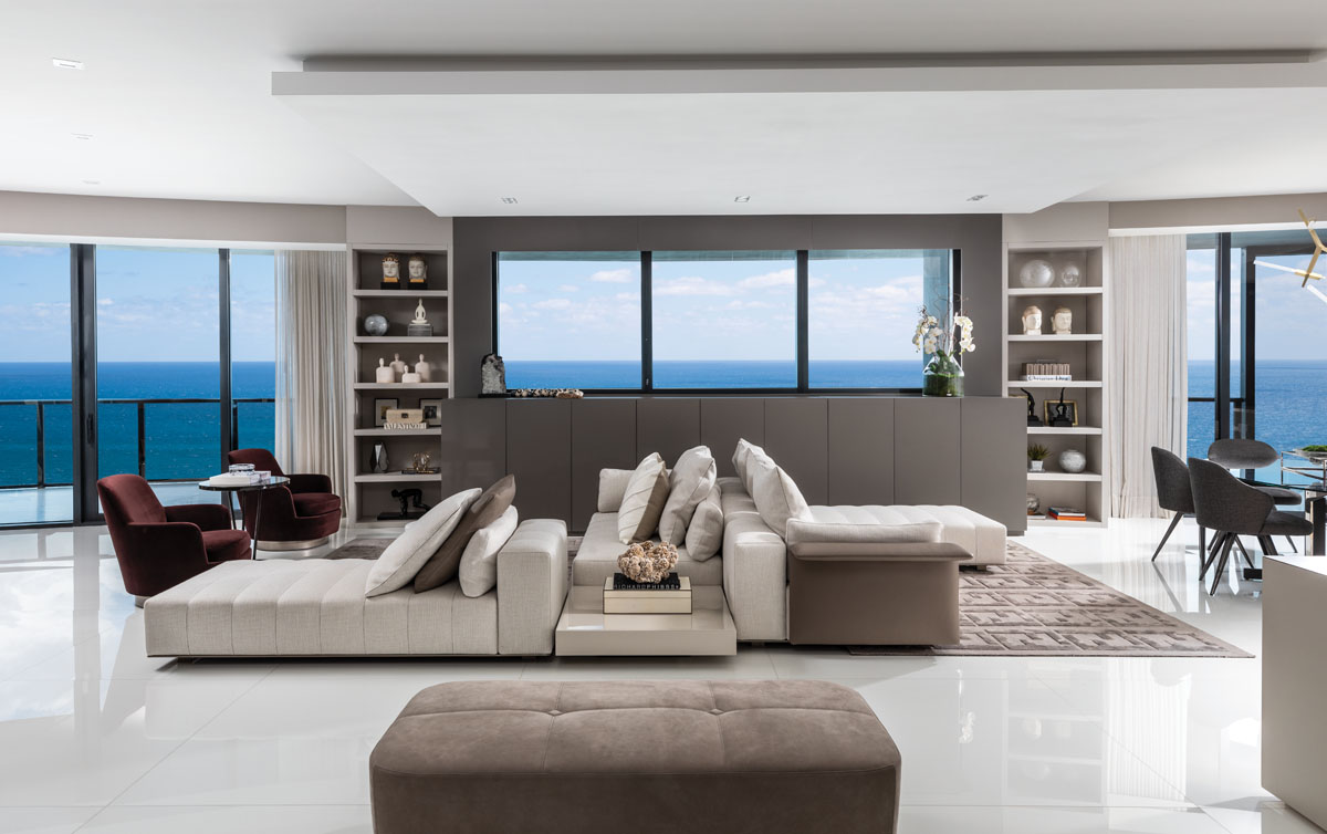 White Nanoglass tile flooring; Minotti's sectional; Raquel Mothé designed the custom gray laminate cabinetry crafted by Oliver; Fendi Casa's taupe area rugs.