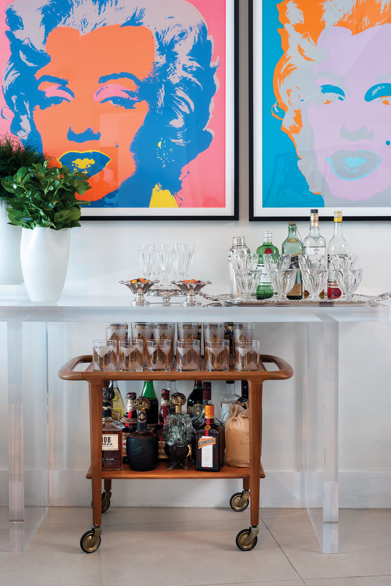 "The bar station acts as a transition space for the designer's parties. ""The 1950s wood bar caddy is quintessentially American and harkens back to a simpler time,"" Ruiz says. Atop KOM's custom console sits a white crystal vase from Two's Company."