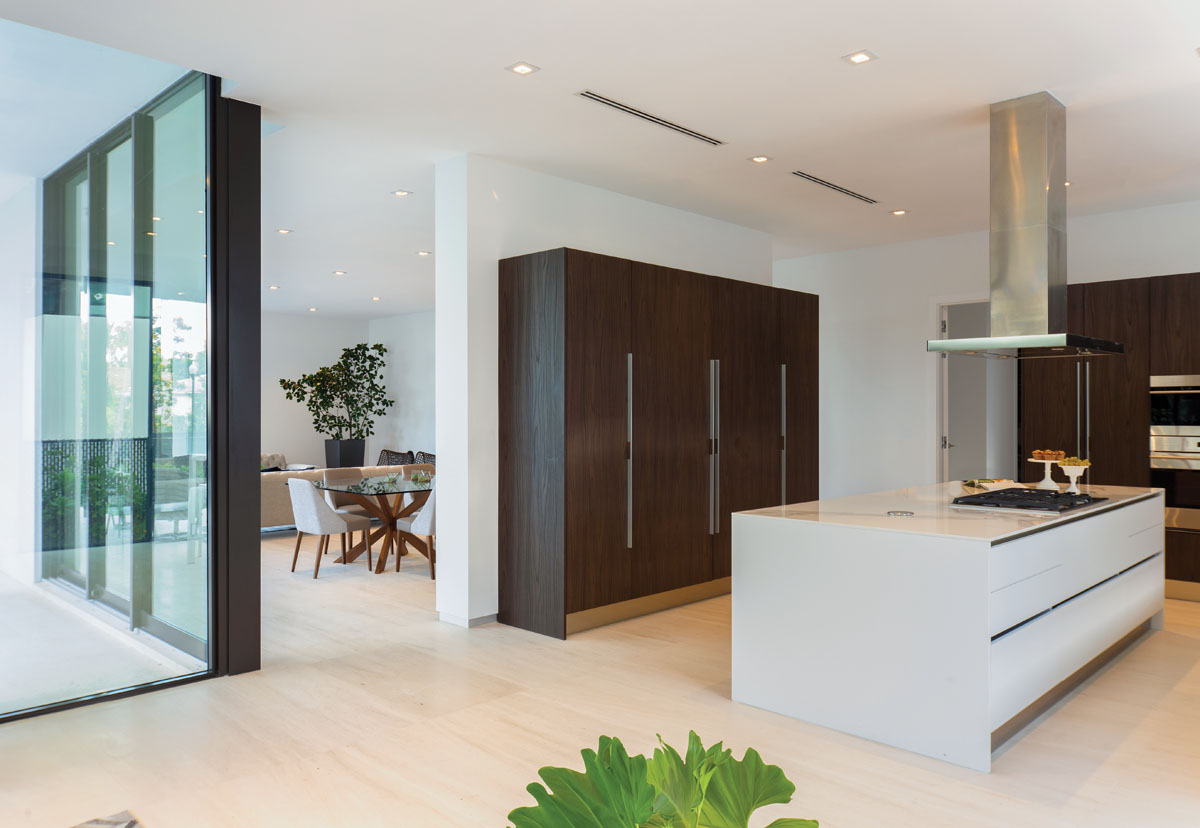 Sleek and minimalist in style, the kitchen is outfitted with Mia Cucina's cabinetry topped in clean, white quartz.