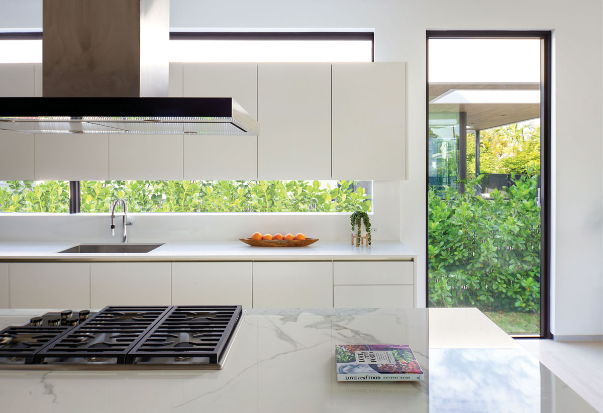 The island shaped of Neolith white porcelain from Fine Surfaces. Wolf's stainless steel hood and double ovens give a modern edge to complete the culinary space.
