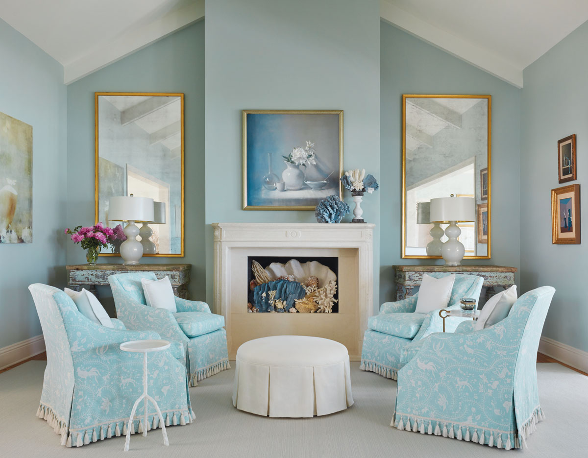 Purchased during a shopping trip to Cote Jardin Antiques in West Palm Beach, a pair of painted console tables flank the fireplace in a sitting area of the living room. The setting continues the cool classic palette with the choice of China Seas textiles and a custom cocktail ottoman.