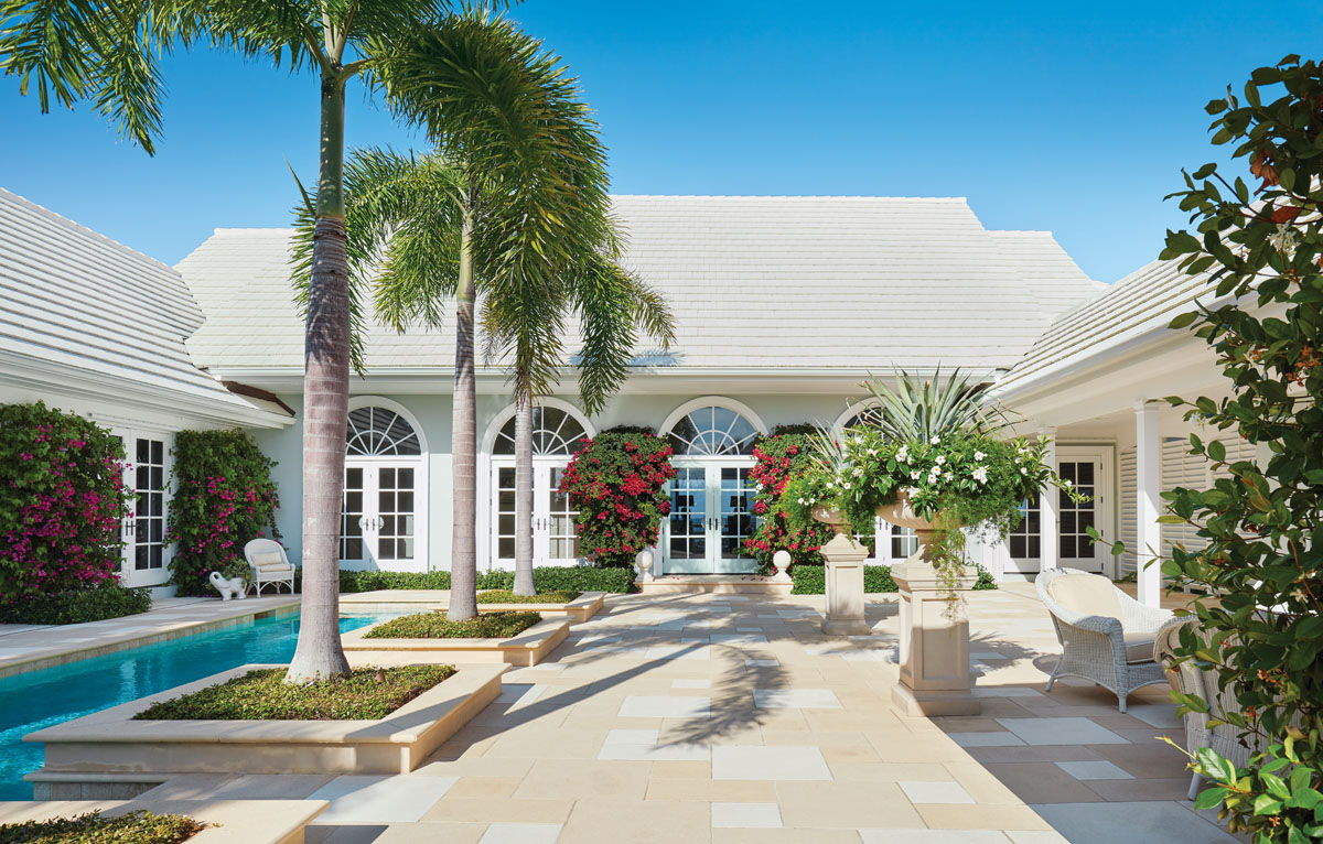 French doors, Palladian-capped windows, and a colonnaded loggia serve as backdrops for indigenous palms, tropical bougainvillea and urns potted with annual flowering plants.