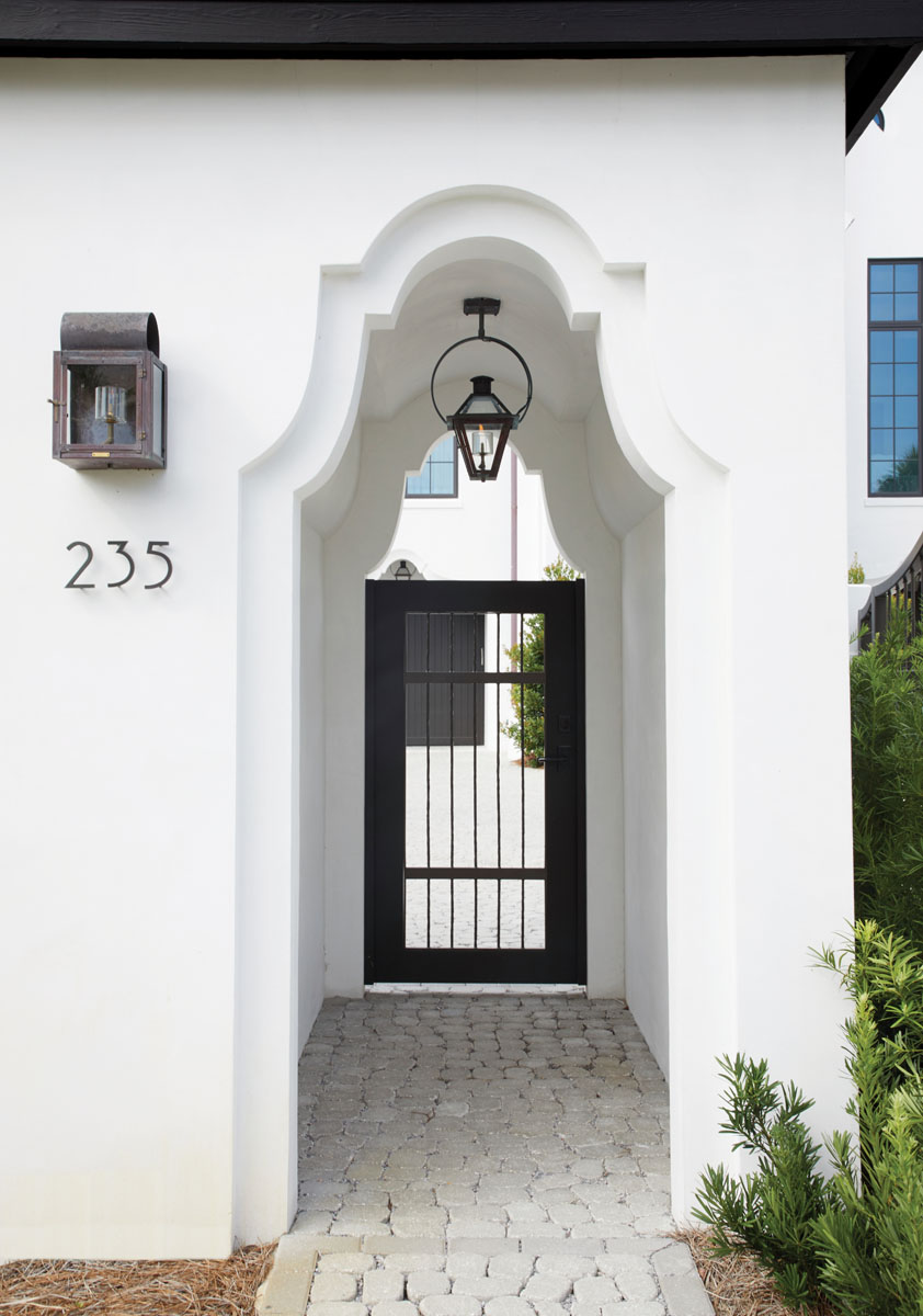 Accentuated with Bevolo copper lanterns, Dutch-influenced stucco detailing, and a custom metal pedestrian gate from Creative Metal Works, this visually inviting pavilion offers a compelling glimpse of the property.