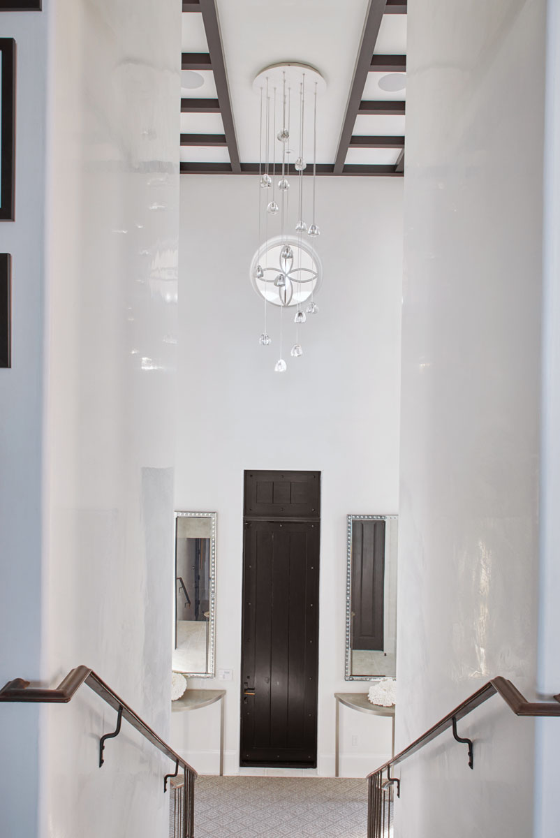 The stairway, with white Venetian plaster walls and custom, bronze handrailings from Creative Metal Works, leads from the main floor down to the front entrance foyer. Lumens' crystal droplets cascade from above.