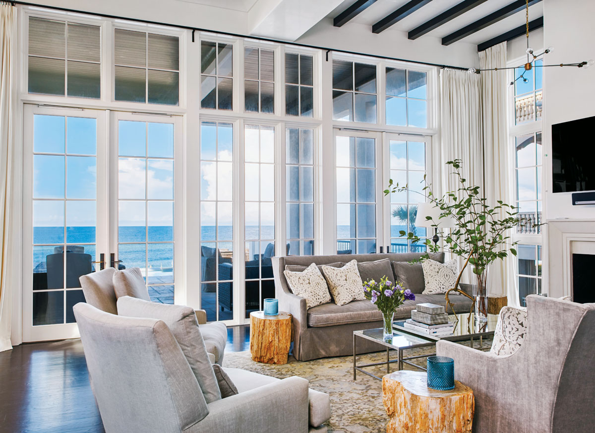 Soaring 12-foot-tall windows and doors in the living room display a panoramic ocean view just beyond the loggia and pool. Plush furnishings include Lee Industries' sofas and chairs, petrified-wood accent tables from Bernhardt and Oly's mirror-topped cocktail table.