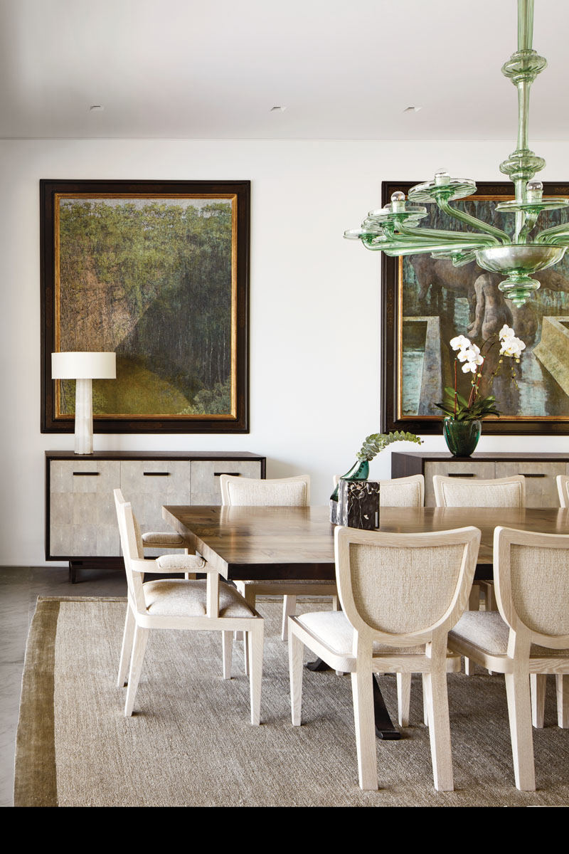 Set aglow by a Murano glass and metal chandelier, the dining room is centered by BDDW's polished wood table of old-growth chestnut and chairs crafted in Paris. Two works by Nicaraguan artist Armando Morales grace the walls.