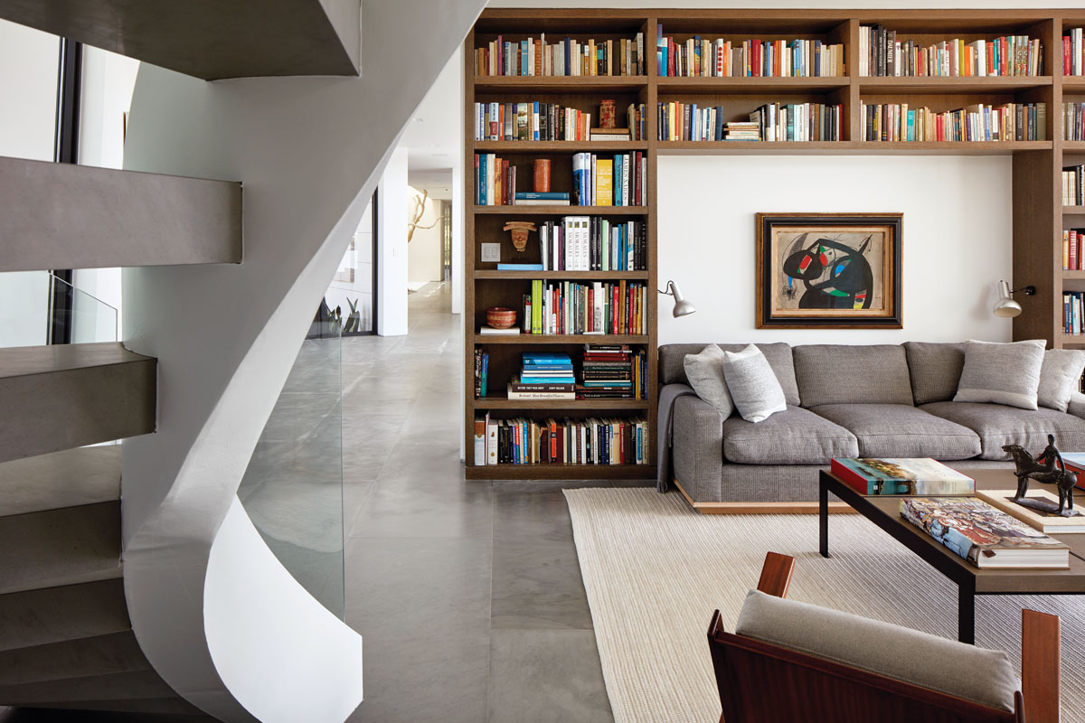 With treads made of massive stone slabs, the library's massive helix-like stairway rises to the husband's office. Set within a niche of books, an oversized sofa in gray linen and auction-purchased midcentury chairs feel familial. A Joan Miró gem centers the bookcase wall.