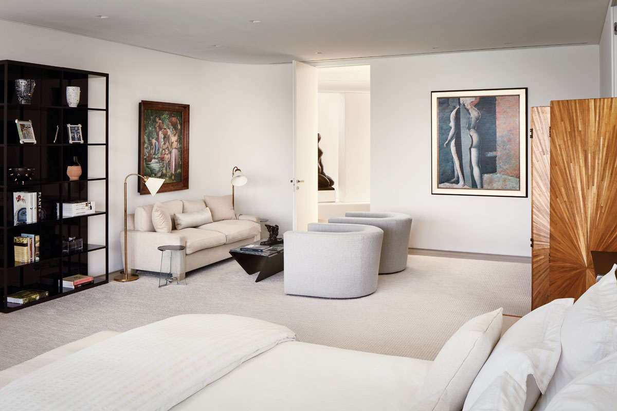 With only the art and a view to distract, the master suite bespeaks serenity in off-white. A plush sofa from de Angelis and a pair of Liaigre chairs huddle together, while a unique, 1930s Jean-Michel Frank screen of straw marquetry stands tall.
