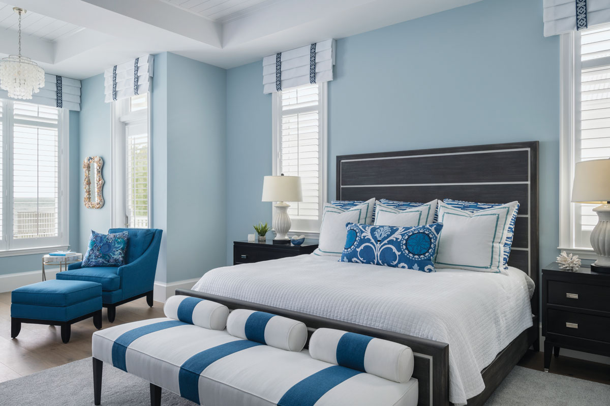 In the master bedroom, the boldly striped bench from Vanguard and the blue tweeds of Fairfield's lounge chair and ottoman brighten the space. Century's java-finished bed fits the island flavor, while white plantation-shuttered windows are crowned by Roman shades with embroidered Celtic knots.