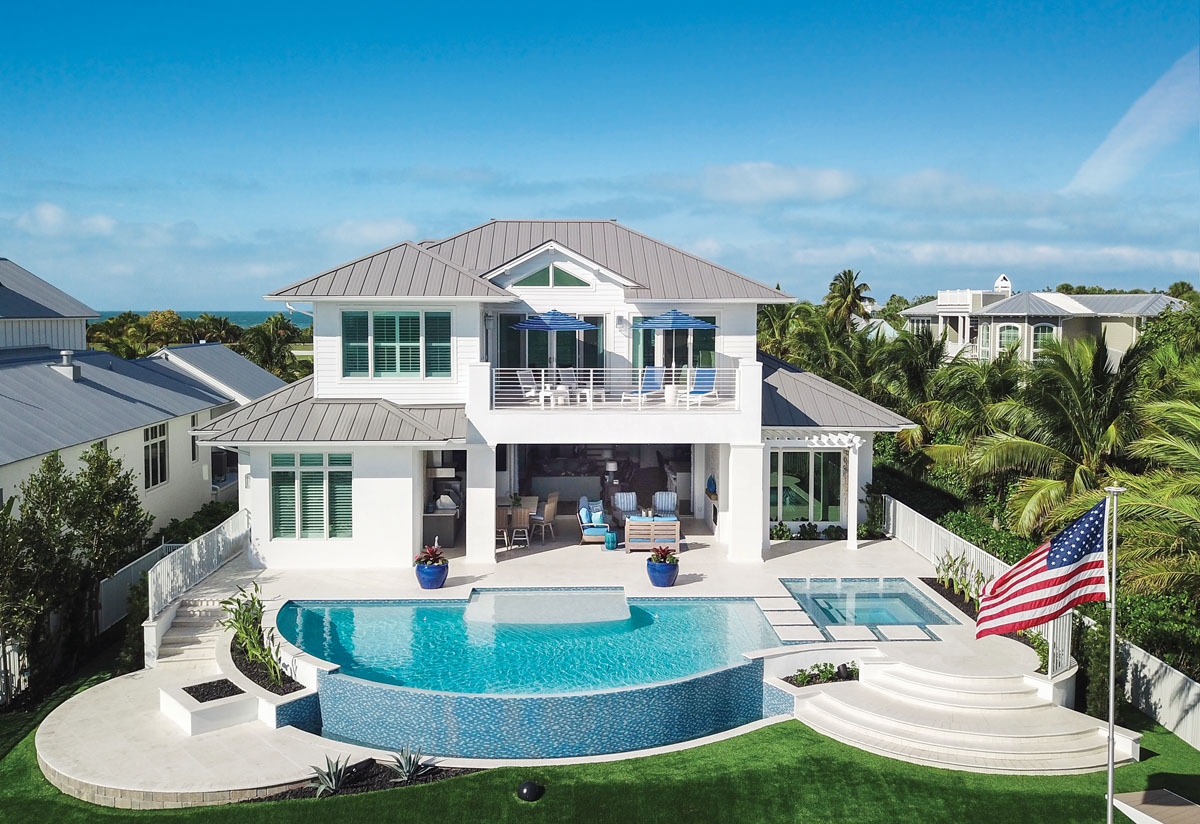 "Encased in sparkling glass mosaic tiles, the half-moon pool and its sister spa by Nassau Pools are joined below by a nearly beachside firepit. Enamored with her home, owner Michele Harrison says, ""I think we'll stay!"""