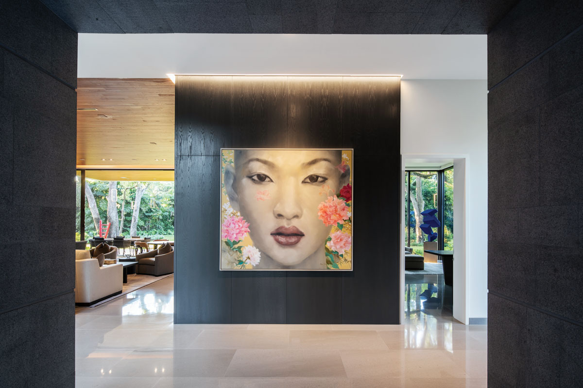 "Almost as if to whisper, ""You're not going to believe the view,"" artist Siew Ying Chong's portrait, Sapphire, beckons as it centers the wood-paneled entry wall. Polished marble flooring stretches toward the living room and the study beyond."