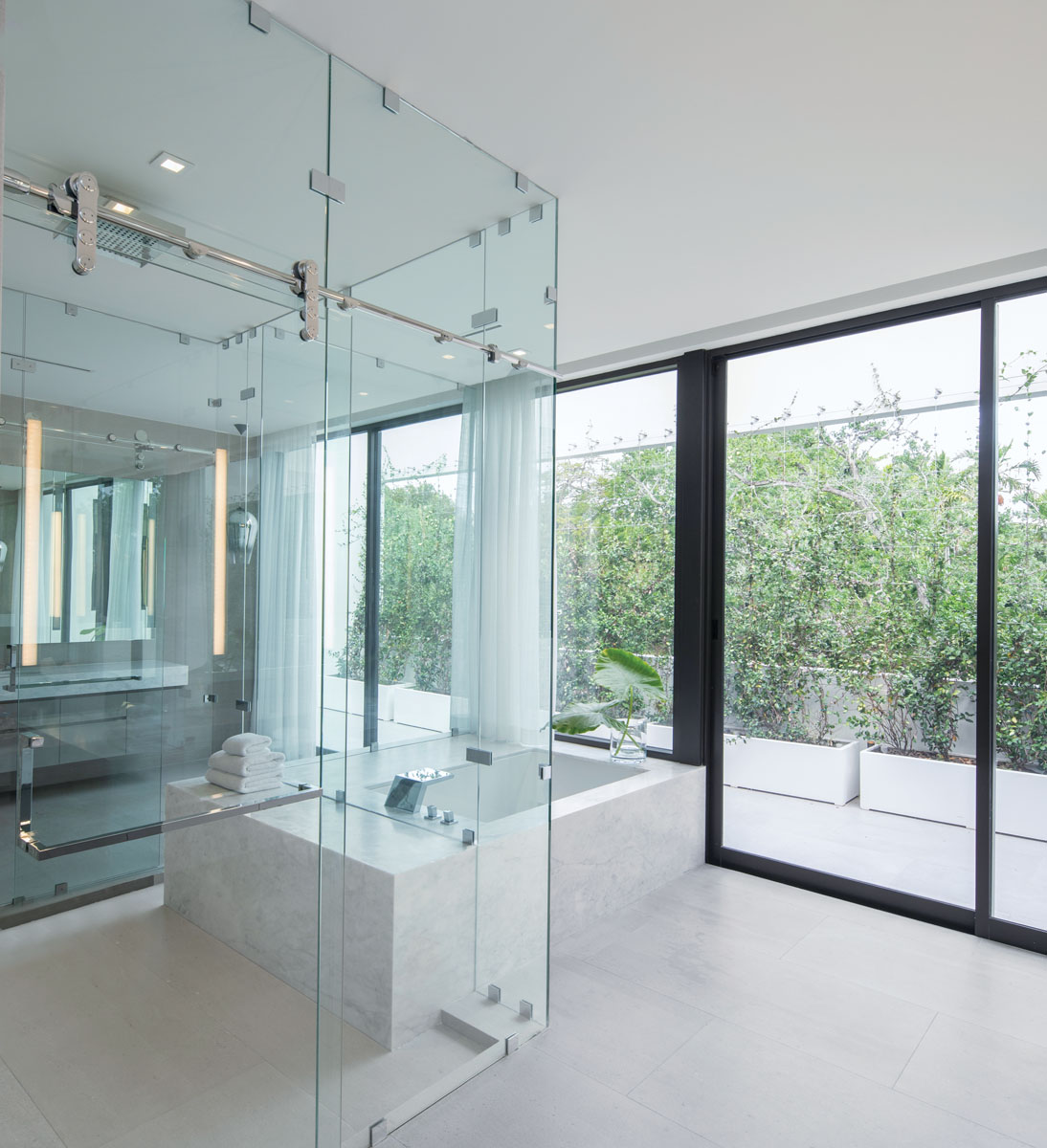 Sheer draperies pull open to welcome natural light into both the bedroom and the master bath, where a marble-clad tub offers spa-like relaxation and rejuvenation.