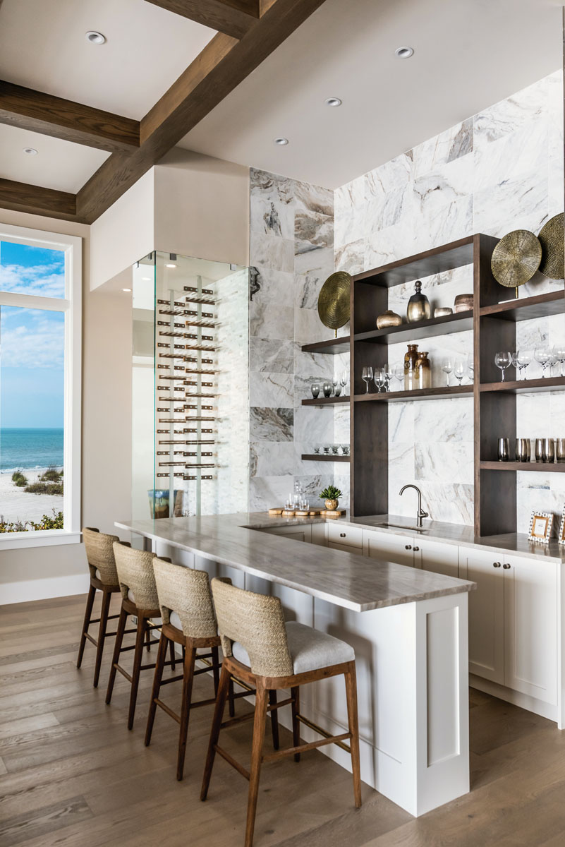 "A wave of Presario's unpolished Lumen White stone from Hadinger wraps the walls in cool comfort. Pulling up to SunMac's leather-finished quartzite countertop, Brownstone's sand-blasted teak ""Beach"" barstools bring the warmth."