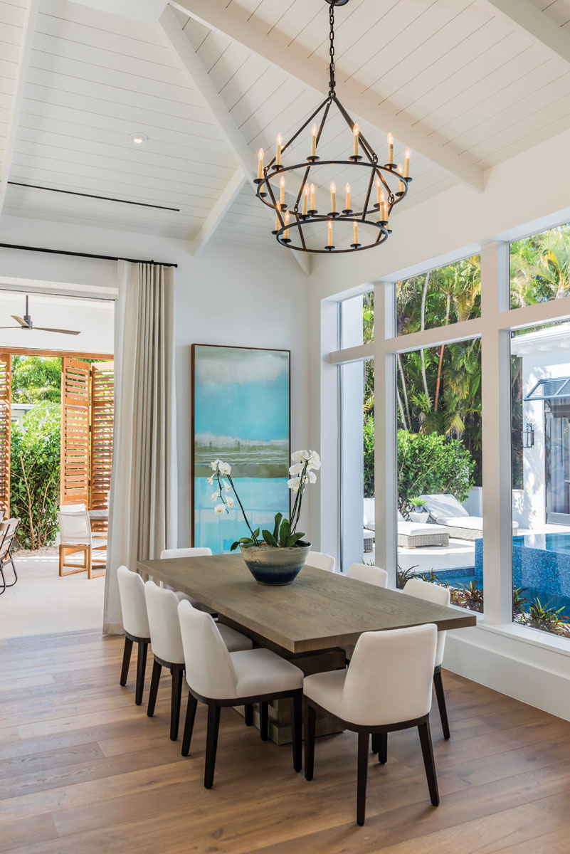 A two-tiered chandelier from Visual Comfort features an open, ringed metal frame that elegantly suspends from the pitched ceiling. Restoration Hardware's cerused gray oak table surrenders to the dining area's informal look, while the aqua hues of a giclée from Wendover Art embraces the tropics.