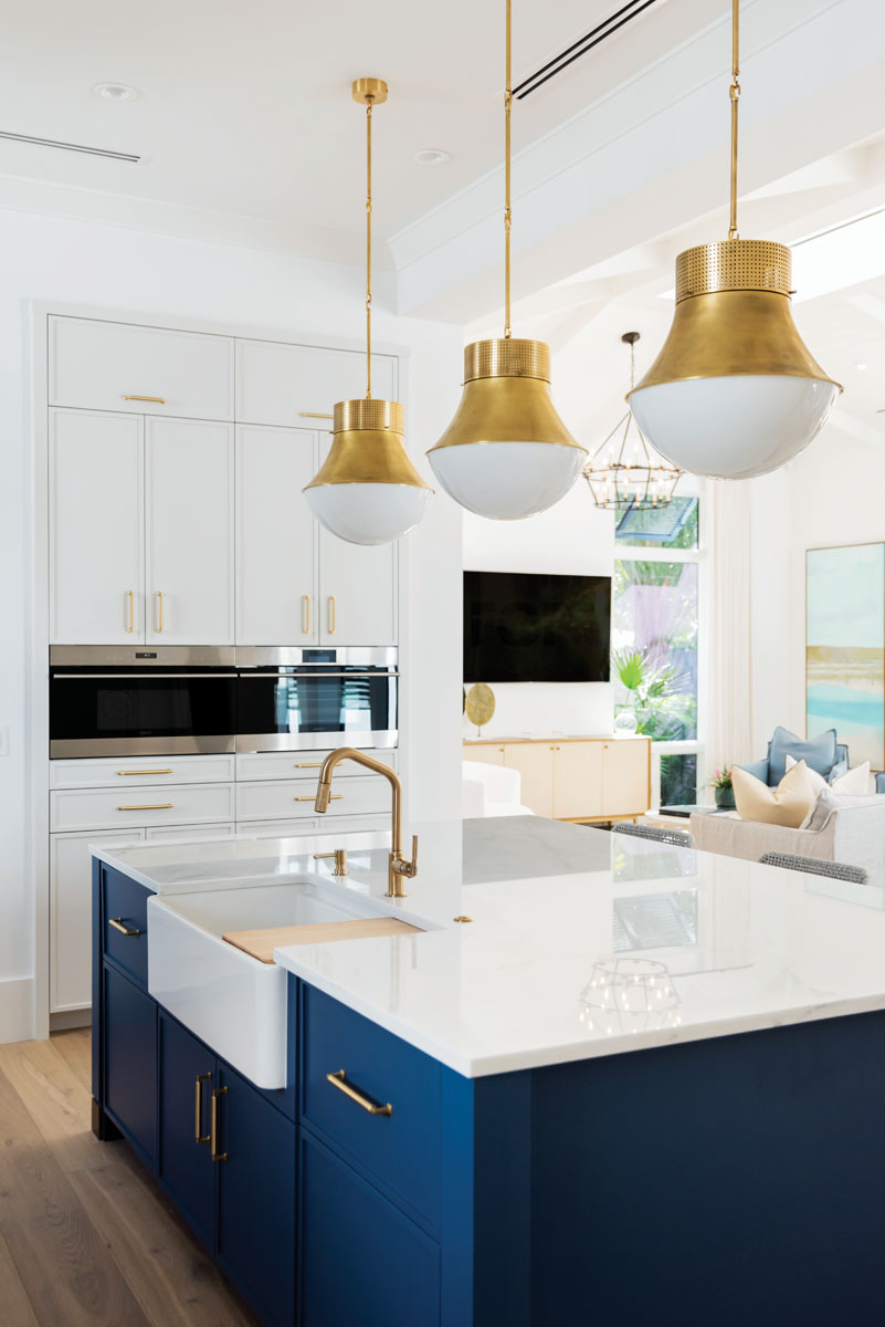 The open, family-friendly kitchen gets elevated style with a handmade Moroccan tile backsplash from Ann Sacks. The finesse continues with Edge Cabinetry's custom hood, crisp white cabinets, and a center island that adds a lively pop of blue.