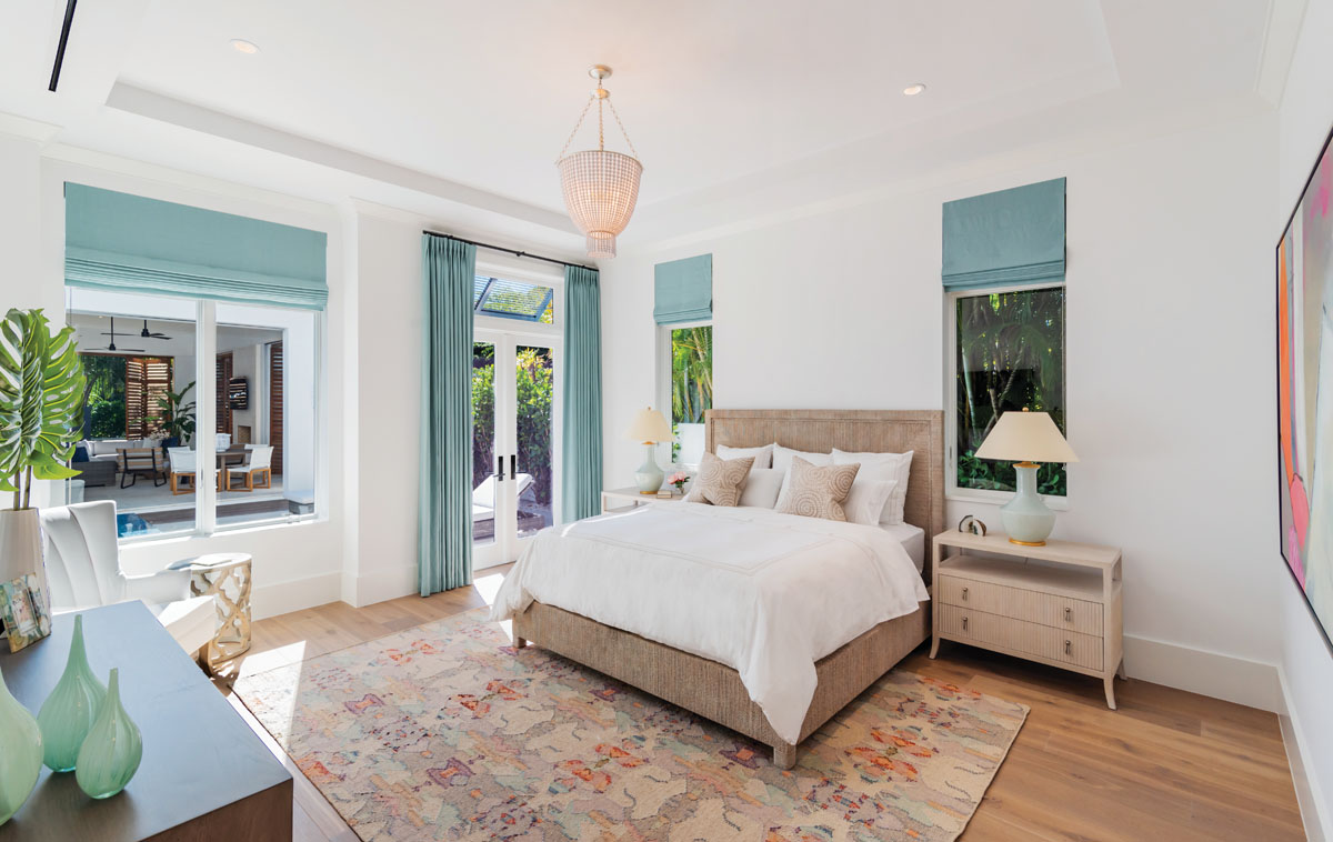 "The master bedroom's island-infused palette features Palecek's ""Woodside"" bed wrapped in woven lampakanai rope and Bernhardt's bedside chests in a cerused linen finish. Seafoam green vases from Tozai Home play off Visual Comfort's beaded chandelier and ice blue ""Lambay"" lamps."