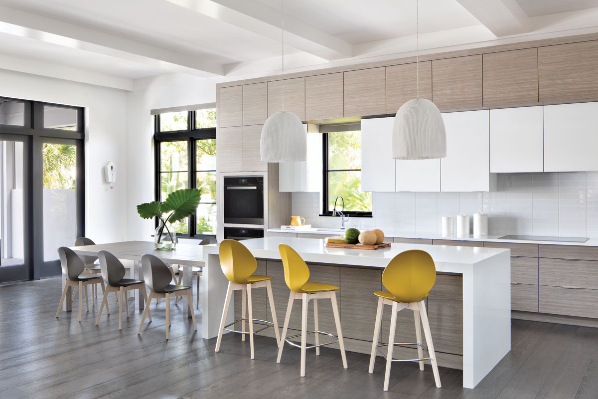 "Streamlined Wood-Mode cabinetry topped in Pompeii quartz runs the expanse of the kitchen. Contoured with a central rib reminiscent of a basil leaf, Calligaris ""Basil"" counter stools and chairs complete both a structural and decorative theme."