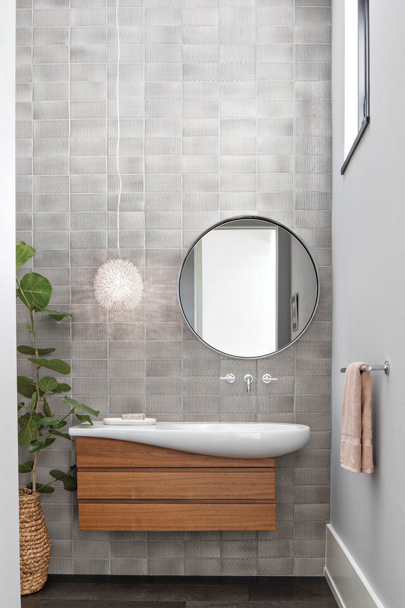 "Laufen's floating vanity and sink provides a visual anchor for the powder room. Here, Arteriors' mirror mimics a porthole as the Varaluz ""Urchin"" light pendant evokes the sea. A wavy wall of textured, gray ceramic backs the coastal modern scene."