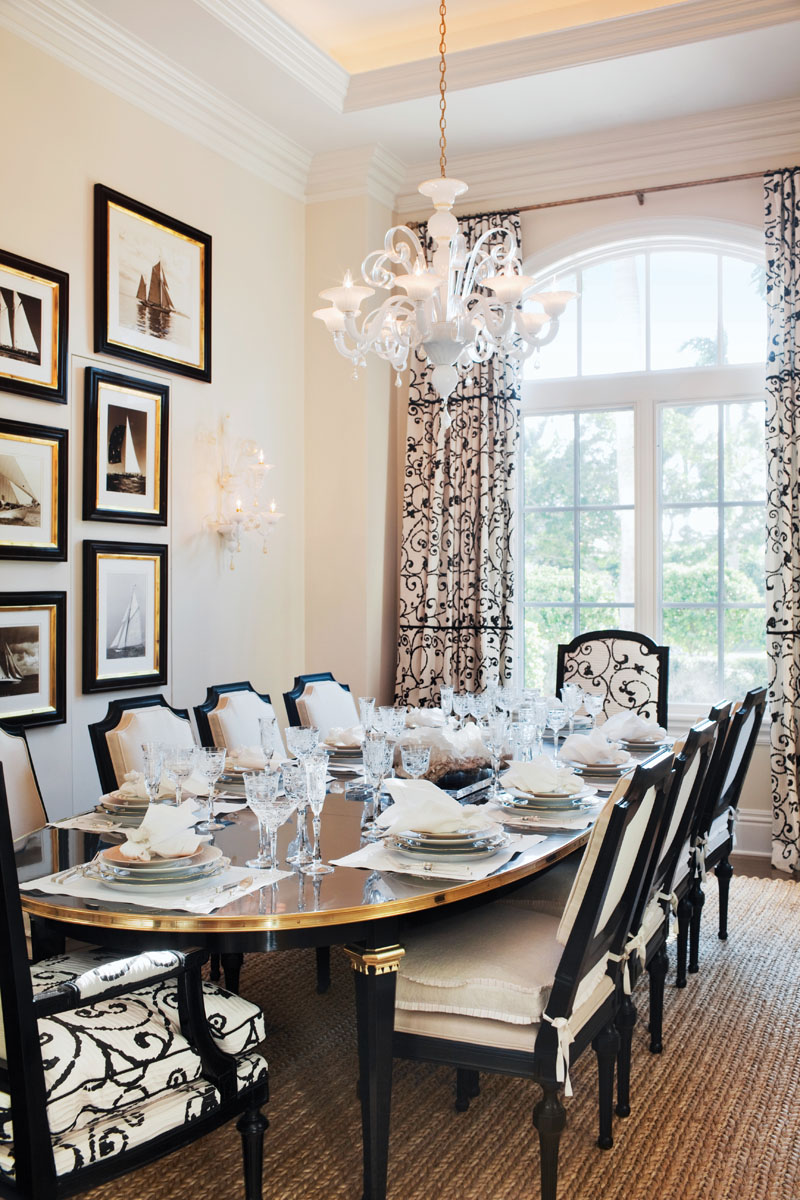 Schumacher's black and white railroaded drapery in the dining room makes a striking backdrop for the vintage Italian chandelier and wall sconces from Valobra Antiques. Ferrell Mittman chairs host the scene where guests are elegantly seated at Maison Jansen's black lacquer dining table from Greenwich Living Antiques.