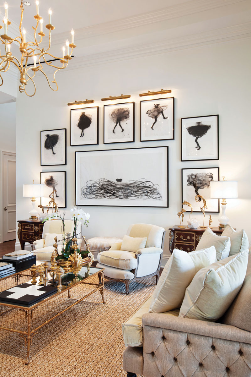 "In the living room, the designer paired Ironware International's gold chandelier from Holly Hunt with vintage Italian table lamps atop antique chests. Arranged in a fun format, original charcoal and pencil on vellum works by Canadian artist Cathy Daley seem to float in the frames. ""The skirts blow in the air, joyful and free-spirited,"" Winters says."