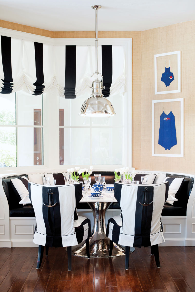 he whimsical breakfast nook delights with a custom black and white banquette and Kravet's boldly striped valance above.