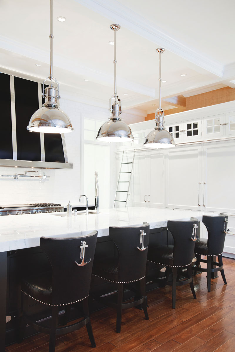 Designed by Winters, the kitchen stuns with crisp, white custom cabinetry crafted by Bona Fide and accented with a black hood framed in stainless steel. Circa's nautical-inspired bulkhead pendants cast circles of light above the marble-topped island flanked by counter stools backed with stylish anchor pulls.