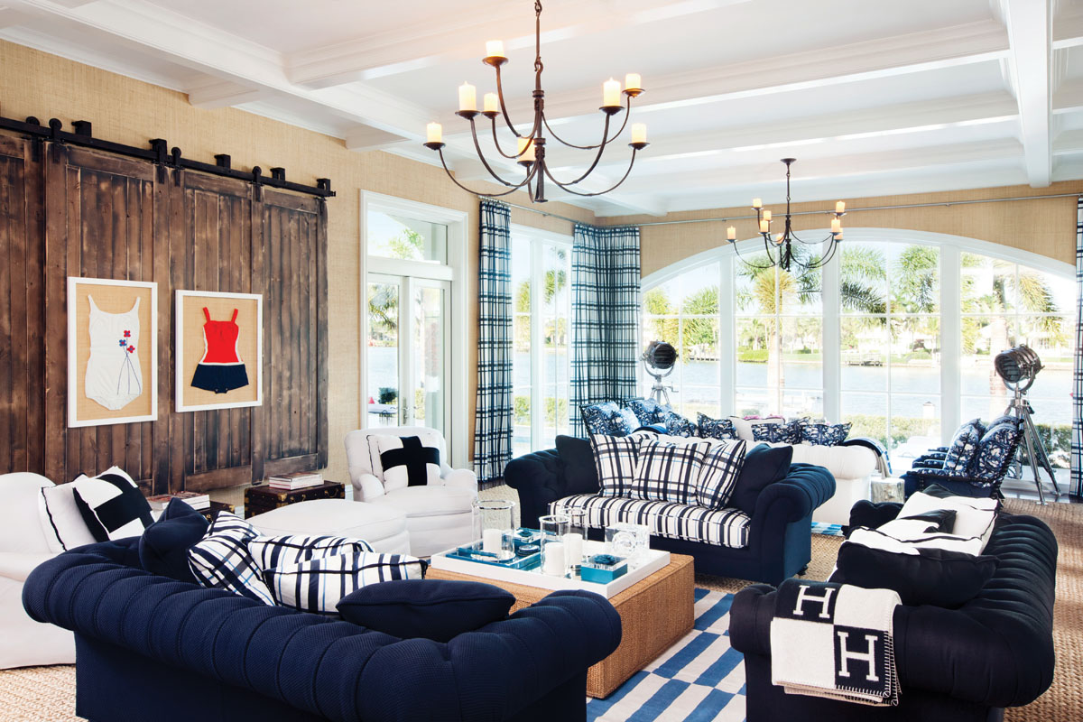 A sophisticated palette creates a flowing pattern that draws the eye around the family room. Striped in blue and white, area rugs from ABC Carpet ground two conversation groupings. Classic Rose Tarlow chandeliers from Holly Hunt unify the flow. Framed swimsuit art from Petrie Point Design enhances the theme.