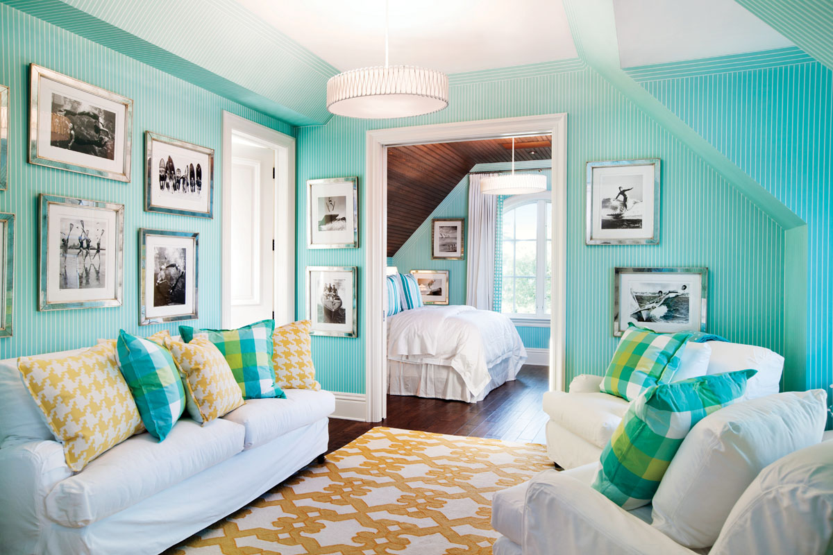 Winters layered the guest suite with a selected mix and match of colorful plaid accent pillows from Kravet and Lee Jofa to scatter atop the white sofa and chairs from Pottery Barn. The charmingly patterned area rug from Anthony, Inc. creates a sunny and happy look. In the rear bed chamber, she designed the headboard in an aqua print with custom aqua pillows.
