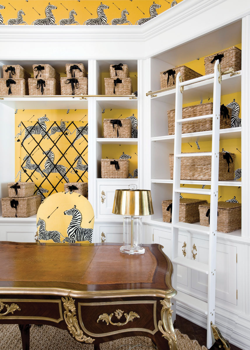 The wife's cheery yellow office is designed with custom white ladders, the Maison Jansen desk, and a cute vintage desk lamp from 1st Dibs. Scalamandre zebra fabric and looks terrific with the matching wall covering.