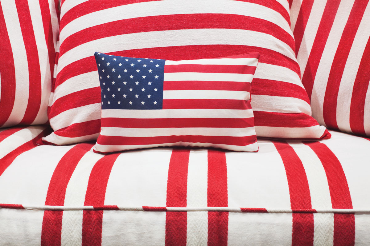 "The red-and-white striped sofa fabric from Kravet is part of the husband's office. ""I picked a closeup of the American flag for the accent pillow fabric because the husband is an unselfish and great American,"" interior designer Megan Winters says."