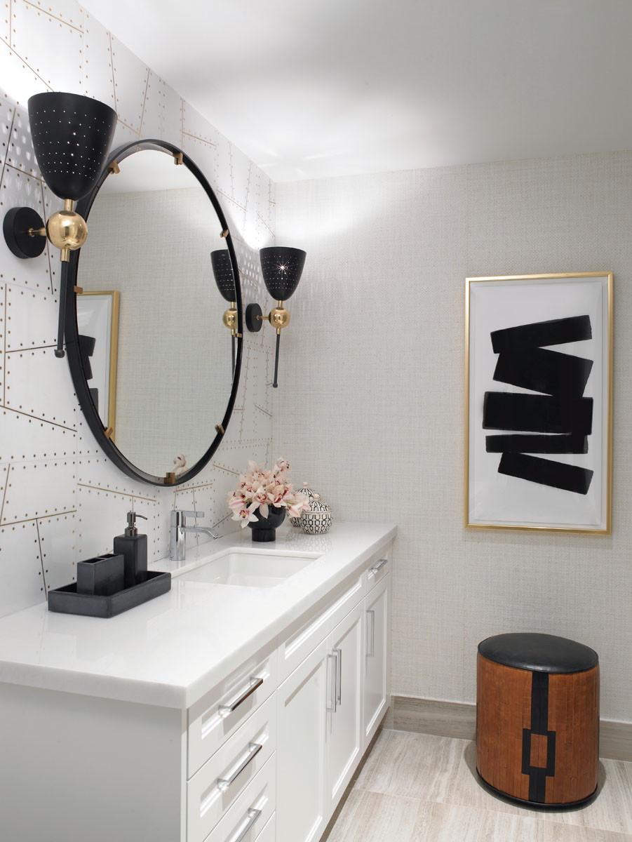 Stark white Thassos marble tops the vanity in the guest bath. A mirror framed in black circles the dramatic backsplash riveted with gold. Wall torchieres fill the private space with resort-style glitz and glam.
