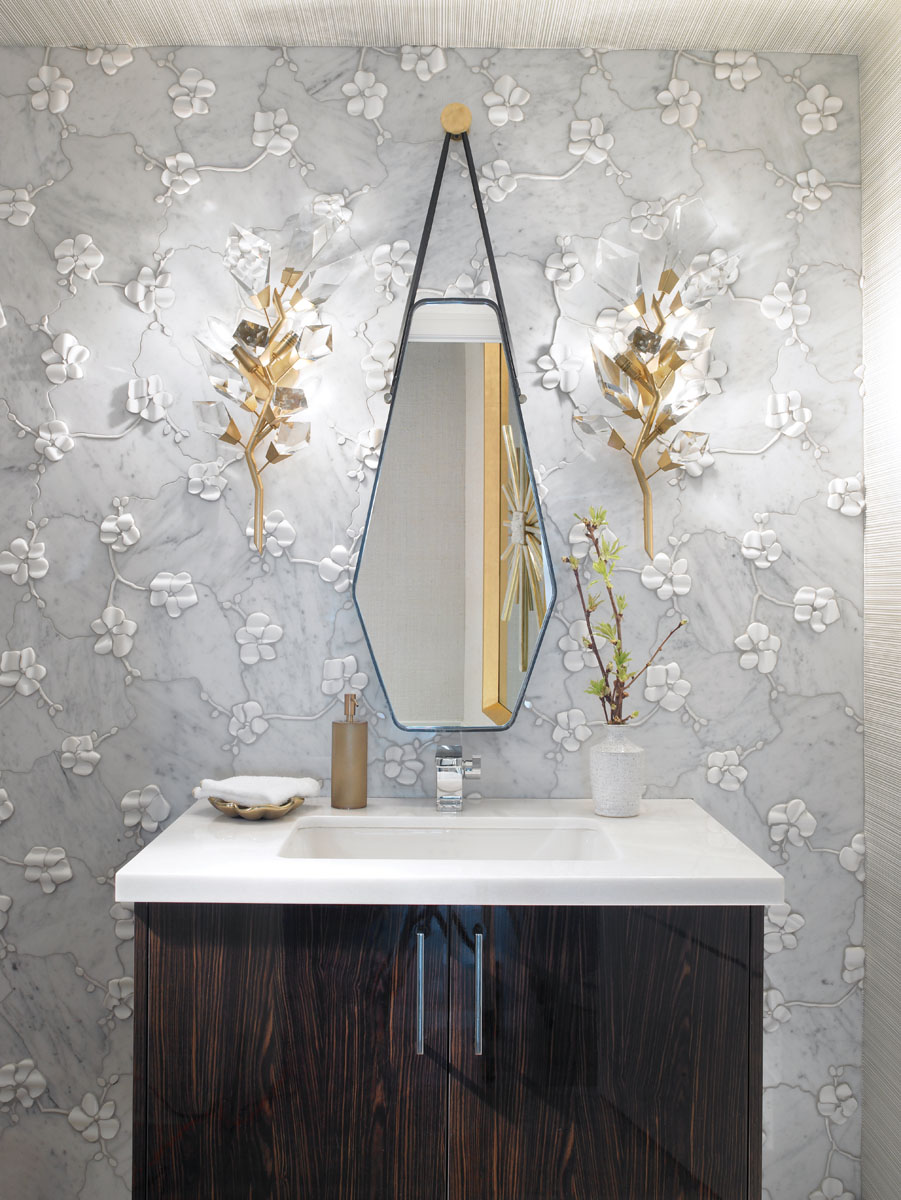 "Extravagantly textured, Michael Aram's sculpted ""Orchid"" wall decor enhances the beauty of the powder room. Fine Art's gold sconces create whimsy in homage to the homeowners' fun and warm personalities."