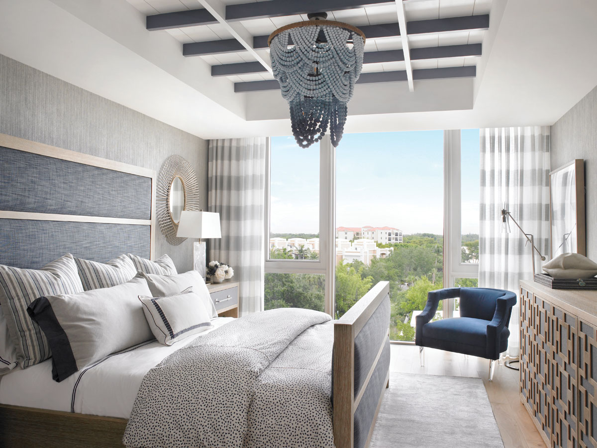 Juxtaposing raw with refined, the guest room melds sophistication and serenity. A highly positioned embellishment, the chandelier features wooden beads in an ombré of white, blue and gray tones.